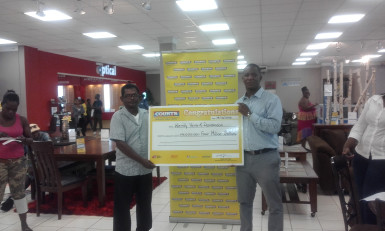 Mr Deonandan (left), one of the $2 million prize winners and Marketing Manager Pernell Cummings pose with the award cheque.