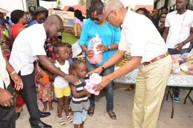 President David Granger (right) presenting toys to the children who assembled at Wilson Gas Station in Buxton Village. (Ministry of the Presidency photo)