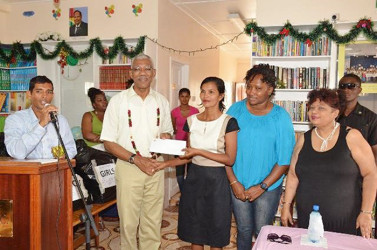 President David Granger (second from left) handing over a cheque for $2M to the Administrator of the Good Hope-Lusignan Learning Centre, Annette Roopchand while Ministers Annette Ferguson (second from right) and Amna Ally (right) look on. (Ministry of the Presidency photo)