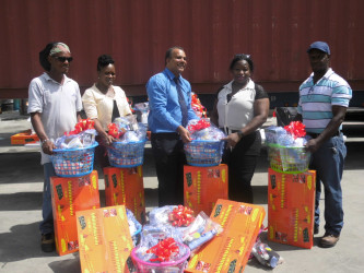 In photo: Chief Executive Officer of Food for the Poor Kent Vincent (centre) poses with representatives of four of the 13 families who lost their homes and possessions in the fire. (Photo by Thandeka Percival.)