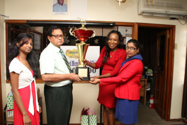 KMTC's Cecil Kennard, receiving Metro's sponsorship package from officials of the company yesterday.