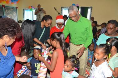 President David Granger distributing toys. (Ministry of the Presidency photo)