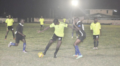 Clive Matthews of Grove Hi-Tech (centre) trying to maintain possession of the ball while being challenged by a Pouderoyen player during their team's matchup at the Farm ground in theStag Beer Super XVI Knockout Championships.