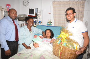 Camanie Kishon, gave birth to her first baby, a boy at Woodlands Hospital on Christmas Day. From left are ANSA Representative Joel Lee, nurse Omodelle Samuels and ANSA Representative Leon Fitzpatrick.