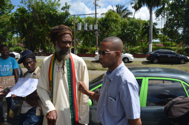 Human rights activist Mark Benschop (right) talking with President of the Rastafari Council of Guyana Ras Simeon (left)
