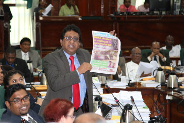 Look, it's here! PPP/C MP Anil Nandlall holding up a copy of yesterday's Stabroek News to make a point in Parliament yesterday. (Keno George photo)