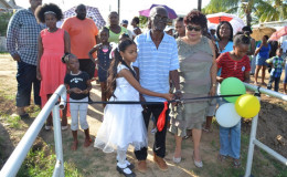 A De Kinderen girl cuts the ribbon to officially commission the bridge in the presence of Minister Amna Ally and residents (GINA photo)