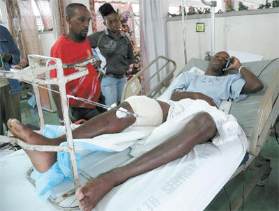 National senior footballer Keron Cummings speaks on his cell phone while warded at the Port-of-Spain General Hospital after being shot in the leg after returning home from a party on Saturday. Cummings was expected to join the national team in camp ahead of the Copa America Centenario match against Haiti on January 8