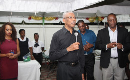 President David Granger, addressing the gathering at Minister of State, Joseph Harmon's (right) home last night. (Ministry of the Presidency photo)