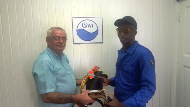 Health and Safety Officer, GWI, Christopher Cathro (left) presenting protective gear to a GWI electrician