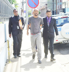 Anthony Smith, centre, is escorted to the Port-of-Spain Magistrates' Court after being slapped with 21 charges related to trafficking a minor and inciting her into prostitution.