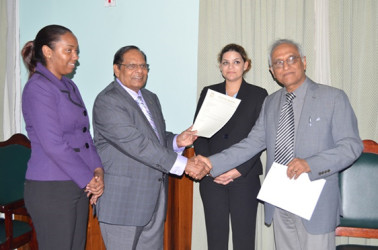 Prime Minister Moses Nagamootoo (second from left) receiving the Guyana Bar Association's Report from its President Christopher Ram. (GINA photo)