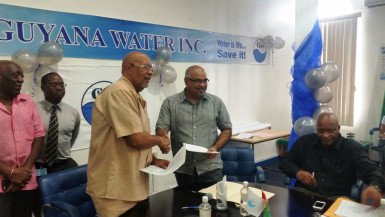 The agreement being exchanged between GWI Chief Executive Richard Van West-Charles (left) and IAST Director Dr Suresh Narine. (GWI photo)