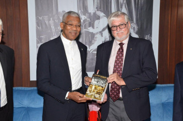 """President David Granger (left) receives a copy of the book""""Hand-in-Hand History of Cricket in Guyana 1865-1897"""" from the insurance company's board member John Carpenter. (Ministry of the Presidency photo)"""