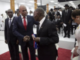Haiti's outgoing President Michel Martelly (2L) shakes hands with the Senate President Jocelerme Privert (C) in presence of the Prime Minister Evans Paul during a ceremony marking the end of Martelly's presidential term, in the Haitian Parliament in Port-au-Prince, Haiti yesterday. REUTERS/Andres Martinez Casares