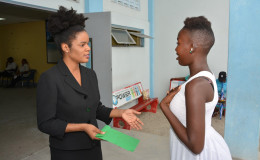 In this Ministry of the Presidency photo, Lloyda Nicholas-Garrett (left) makes the presentation to Cidel Hector.