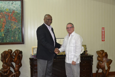 Cuban envoy, Julio Cesar Gonsalez Marchante (right) meeting with Minister of State, Joseph Harmon, today. (Ministry of the Presidency photo)