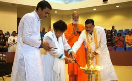 Minister of Social Cohesion, Amna Ally (second from left), Executive Member of the Viraat Sabhaa Guyana, Pandit Haresh Tewari, (left) Swamiji Kaivalyananda Saraswati (third from left) and President of the Viraat Sabhaa, Pandit Rabindranath Persaud, participate in the lighting of a ceremonial lamp. (Ministry of the Presidency photo)