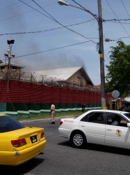 Smoke emanating from one of the buildings in the Camp Street prison today, where nine fires were set.