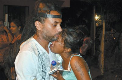 Shayas Khan, left, comforts his wife, Vishma Bissoon, outside their home at Jameel Street, Charlieville, following the death of the couple's six-month-old son, Maleek Khan, yesterday.