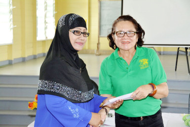 First Lady,  Sandra Granger presenting Latchmin Azeez with a letter of approval for a grant for theBushlot-Armadale Women's Group (Ministry of the Presidency photo)
