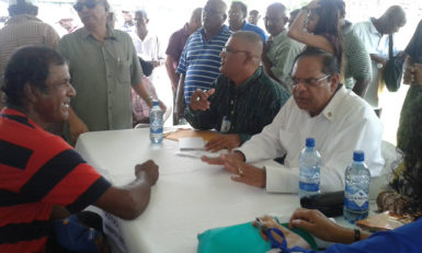Prime Minister Moses Nagamootoo (seated, right) reacts as he listens to a resident's concerns yesterday's 'Meet the Public Day' in Corentyne, Berbice
