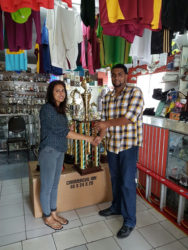 Devi Sunich presenting the champion's trophy of the feature D and Lower event of the Labour Day Classic to Nasrudeen Mohamed (Jumbo Jet Jr.) on Thursday at the Trophy Stall.
