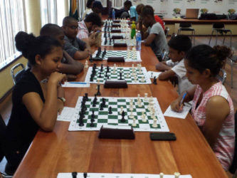 Christ Church Secondary School student Nellisha Johnson (left), ponders as she decides on her next best move against University of Guyana graduate and the Ministry of Housing's Shazeeda Rahim during the Engineering and Construction Incorporated (ECI) chess tournament. Nellisha resides in Orealla, some 60 miles up the Corentyne River and learnt chess in her village four years ago. She won the trophy for the Best Junior Female player in the ECI competition. (Chess photos by Ryan Singh)