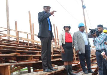 Public Infrastructure Minister David Patterson (left) explaining some of the works to be done on the stands with Minister Annette Ferguson (middle) and Larry London (right), who formerly spearheaded the works at the troubled site