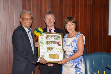 Baroness Dawn Primarolo receives a token of appreciation from Minister of Education, Dr. Rupert Roopnaraine at the end of the session today at the Ministry of the Presidency. Nigel Evans, another member of the delegation is at the centre. (Ministry of the Presidency photo)