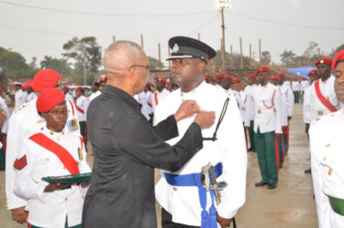 President David Granger, who is also Commander in Chief of the Armed Forces, pins a medal on an officer of the Guyana Police Force. (Ministry of the Presidency photo)