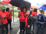 Ministers in the Ministry of Finance and Public Infrastructure, Jaipaul Sharma and Annette Ferguson sharing an umbrella at yesterday's rain-soaked May Day.