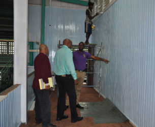 Director of Sport, Christopher Jones (right) makes a point during yesterday's inspection of works at the Cliff Anderson Sports Hall in the presence of GABF President, Nigel Hinds (centre) and Facility Manager, Bashur Khan.