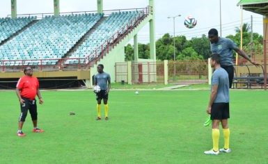 Head-coach Jamal Shabazz (right) conducting a defensive drill with members of his Golden Jaguars rearguard at the National Stadium at Providence