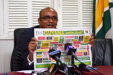 Opposition Leader Bharrat Jagdeo holding up a government advertisement highlighting its achievements over the last year.