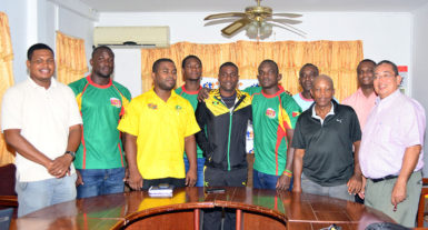 Captains Richard Staglon and Hubert Thomas (centre) embrace in the presence of President of the GRFU, Peter Green (right), Jamaica Manager Tezra Sannister (3rdleft) and members of Guyana's squad yesterday at Olympic House. (Orlando Charles photo)