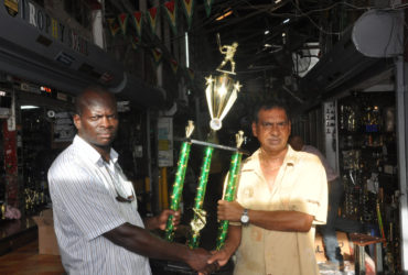 Trophy Stall's Managing Director Ramesh Sunich (right) presents the trophy for the winning team to Samuel Kingston, organizer of the competition.