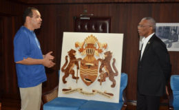 Jonathan Locke (left) explains to President David Granger the effort which was expended to create the work (Ministry of the Presidency photo)