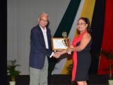 Minister of Education, Dr. Rupert Roopnaraine presents an award to Rita Fox, outstanding educator from Region Ten (GINA photo)