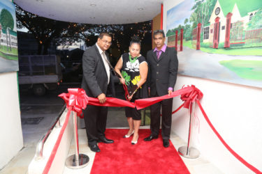 Mayor of Georgetown Patricia Chase-Green (centre) cuts the ribbon to open the new Tower Suites while Guyana Tourism Authority Director Indranauth Haralsingh (left) and Tower Suites Operations Manager Mr Hemraj (right) look on.