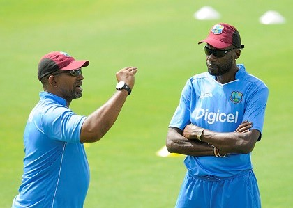 IN BETTER TIMES: West Indies coach Phil Simmons (left) chats with Sir Curtly Ambrose during a training session.