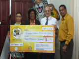 Minister of Public Telecommunications Catherine Hughes (second from left) receives a cheque from Vladimir Permyakov (second from right) Head, Bauxite Company of Guyana/Rusal (GINA photo)