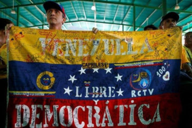 Opposition supporters hold a Venezuelan flag that reads 'Venezuela free and democratic' during a peaceful rally to demand a referendum to remove President Nicolas Maduro in Caracas, Venezuela June 12, 2016. Reuters/Ivan Alvarado
