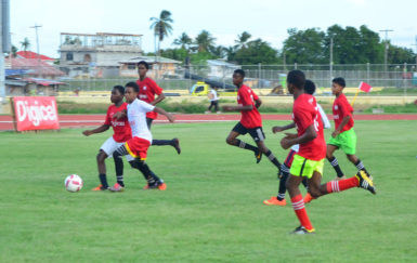 Action between Diamond Secondary (red) and Soesdyke Secondary (white) in the Digicel Football Schools Championship at the Leonora Sports Facility.