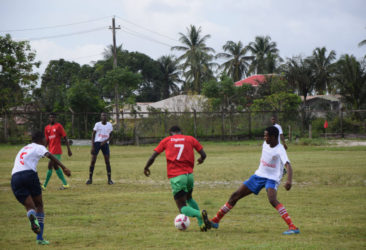 Action between Mackenzie HighSchool (red) and Wisburg Secondary in the Digicel Schools Football Championship at the WisburgSchool ground