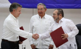 Cuba's President Raul Castro (C) looks as Colombia's President Juan Manuel Santos (L) shakes hands with FARC rebel leader Rodrigo Londono, better known by his nom de guerre Timochenko, after signing a historic ceasefire deal between the Colombian government and FARC rebels in Havana, Cuba, June 23, 2016. REUTERS/Alexandre Meneghini
