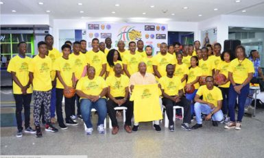 GABF President Nigel Hinds (sitting centre) displaying an official team jersey in the presence of Director of Sport Christopher Jones (2ndfrom left sitting) while members of the Guyana Boys and Girls u16 squads and management staff look on