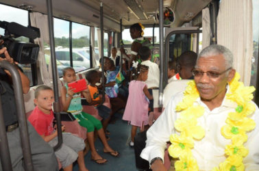 Checking out the school bus: President David Granger (right) seated in the David G No. 10 with children of Coomacka. (Ministry of the Presidency photo)