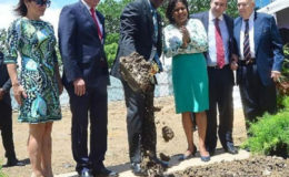 Prime Minister Keith Rowley attended by assorted dignitaries doing sod-turning duties at the site of the planned car park.