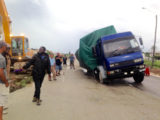 This truck, laden with rice, fell into a pothole at Uitvlugt, West Coast Demerara this morning, where road construction is in progress. It resulted in a disruption of traffic and senior officials of the project visited the scene to bring the situation under control. An excavator also had to be summoned to assist in getting the truck out.